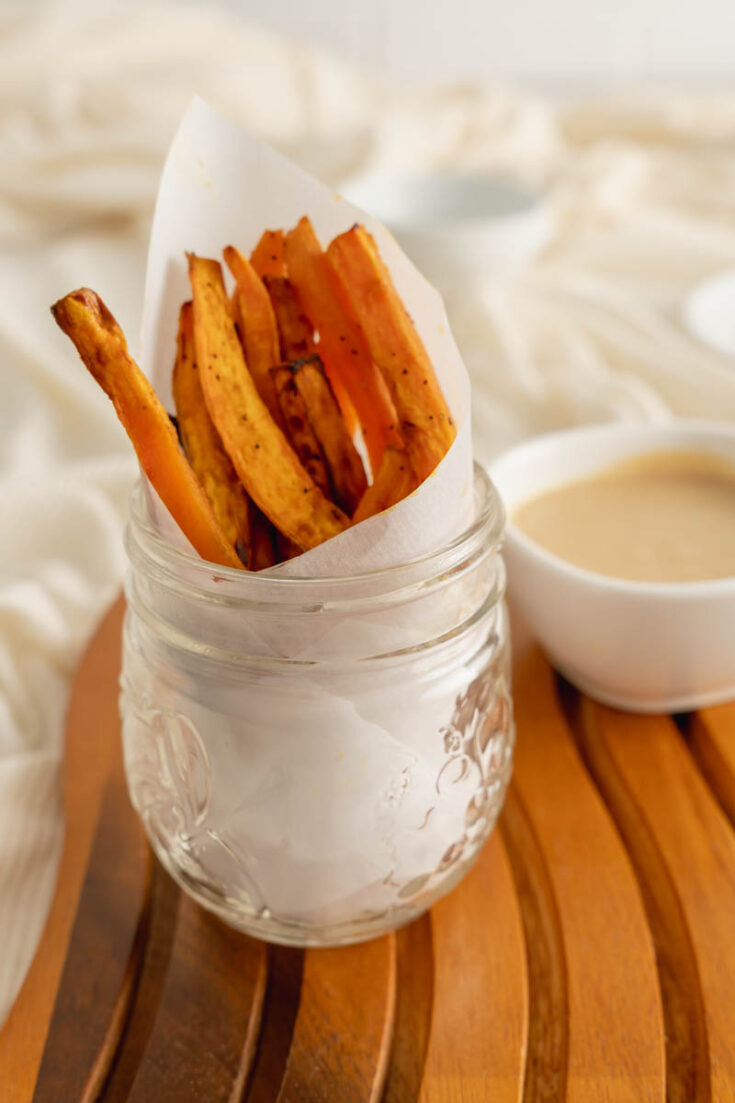 Air Fryer Sweet Potato Fries in a mason jar with a side of cinnamon sugar dipping sauce.