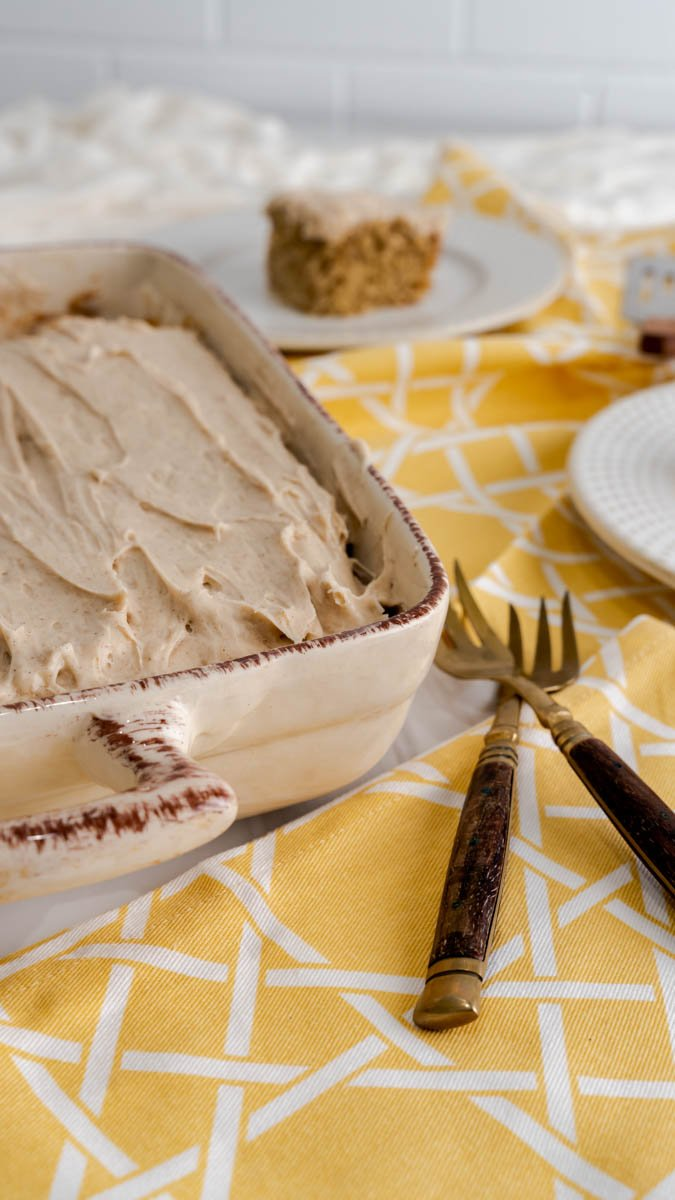 Banana cake with cinnamon cream cheese frosting in 3x9 ceramic baking dish.