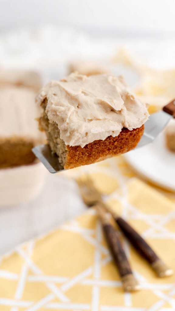 A slice of banana cake with cinnamon cream cheese frosting resting on a cake serve with a wooden handle.