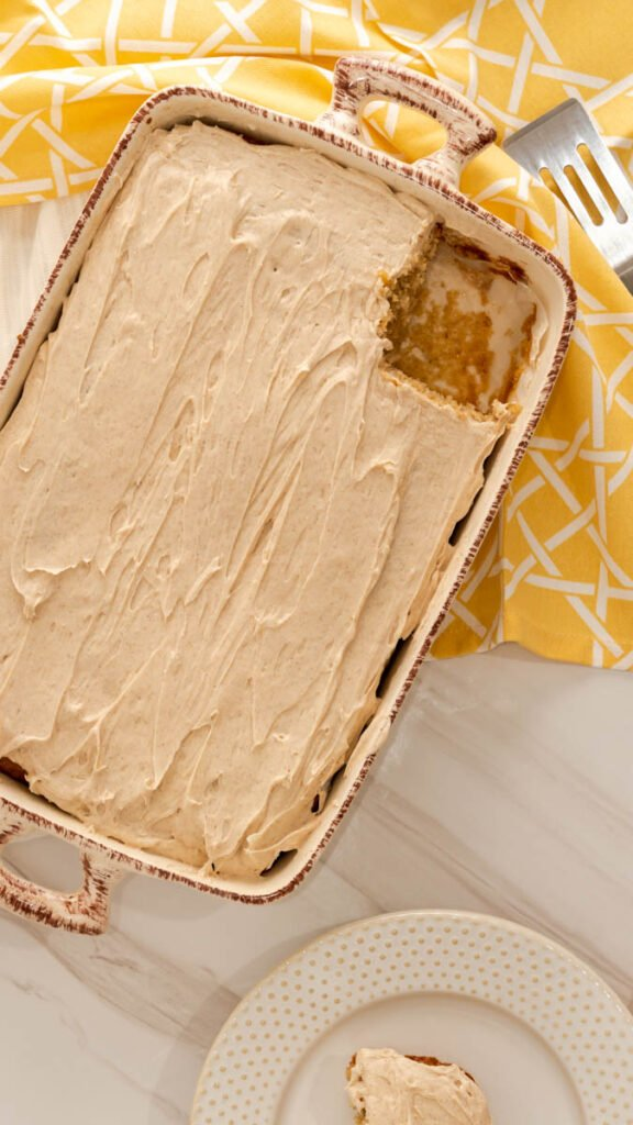 A slice of banana cake cut out of 13x9 baking dish frosted with cream cheese frosting.