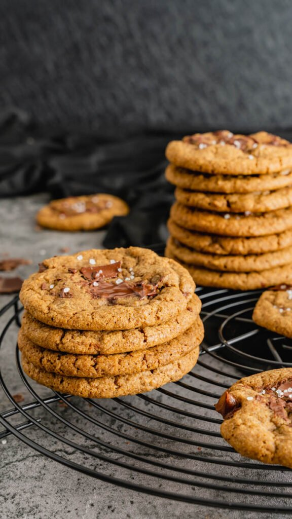 Stacks of cookie with melted chocolate on top resting on a round cooling rack.