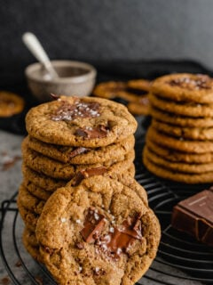 A stack of chocolate espresso cookies on a black wire rack.