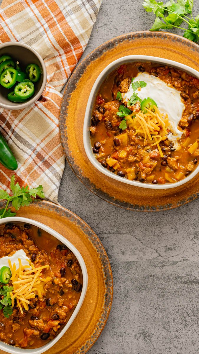 Two bowls of Instant Pot Pumpkin Chili with turkey and black beans in rustic bowls.