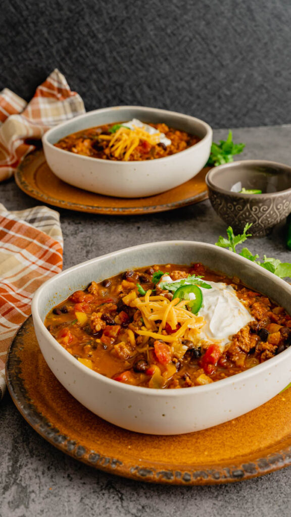 A table setting of two bowls of pumpkin chili sitting on rustic plates.
