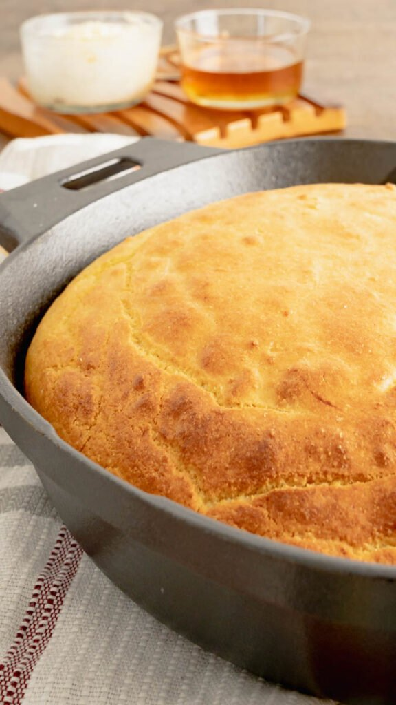 A side view of buttermilk cornbread in a cast iron skillet with handles.