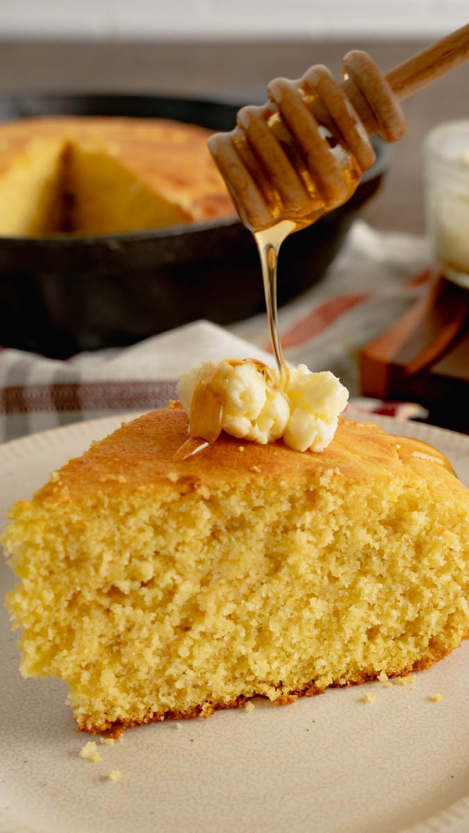A slice of skillet buttermilk cornbread with a dallop of whipped butter and drizzled with local honey.