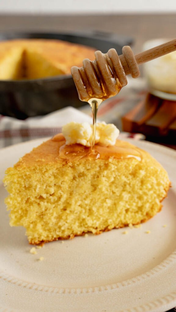 A honeycomb stick drizzling honey on a whipped butter resting on a slice of cornbread.