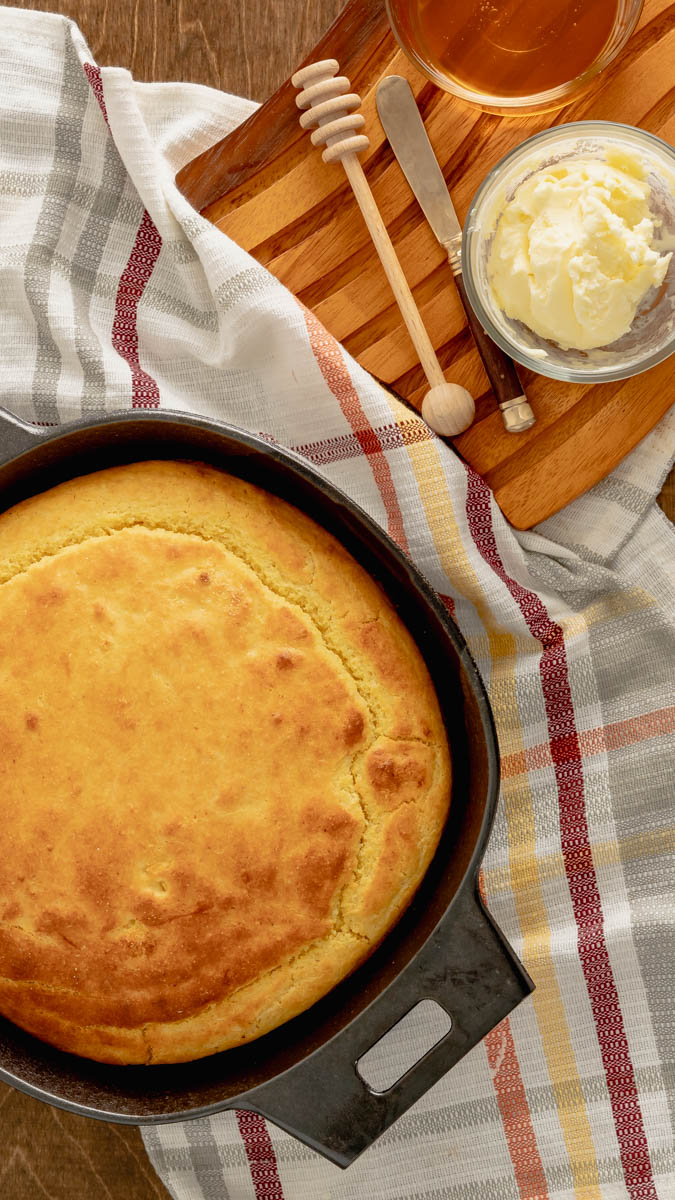 Buttermilk Cornbread made in a cast iron skillet and served with whipped butter and local honey.