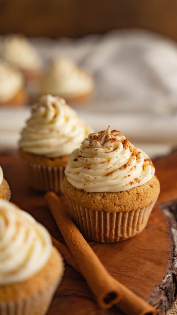 Spice cupcakes with cream cheese frosting on wooden board with cinnamon sticks.