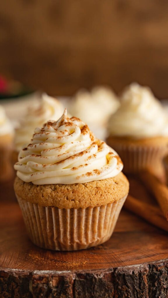 Close up of spice cupcake in white wrapper frosted with cream cheese and decorated with cinnamon.