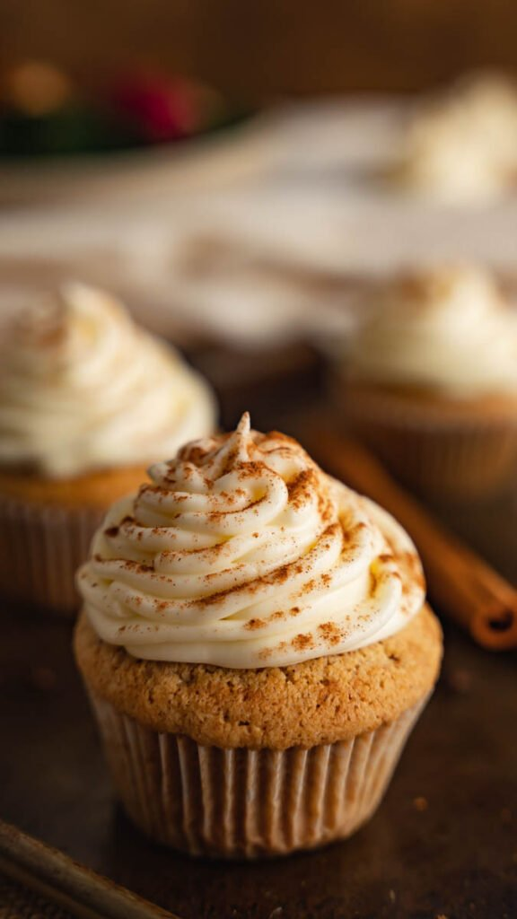 Three cupcakes with frosting that are garnished with cinnamon on dark board.