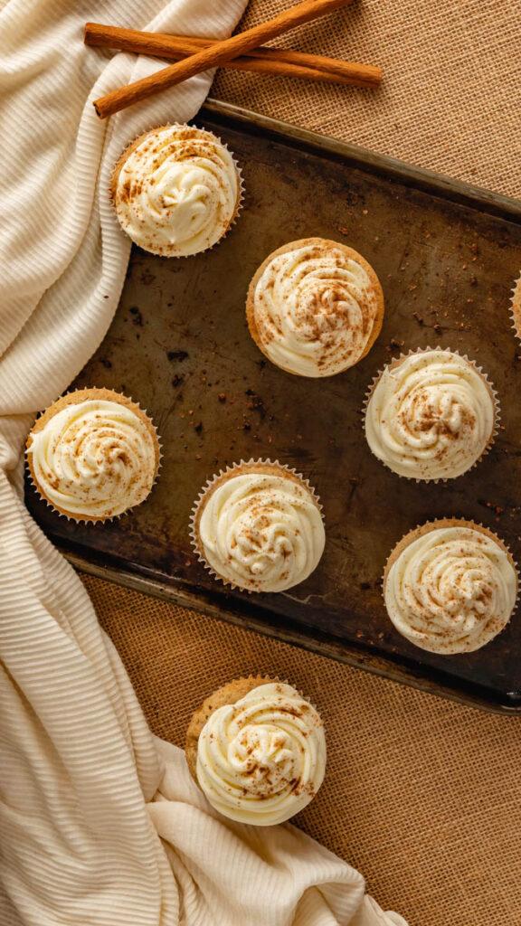Cupcakes sitting on rustic baking sheet.