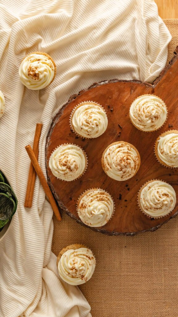 Seven cupcakes on a wooden circular platter with a white linen underneath.