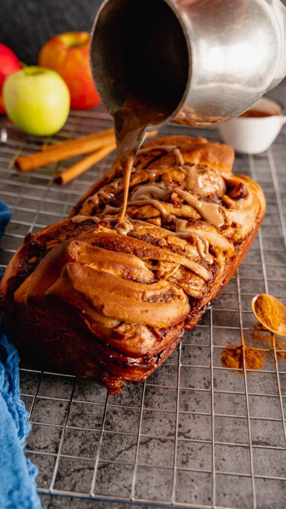 Cinnamon glaze being drizzled onto the warm apple cinnamon babka loaf.