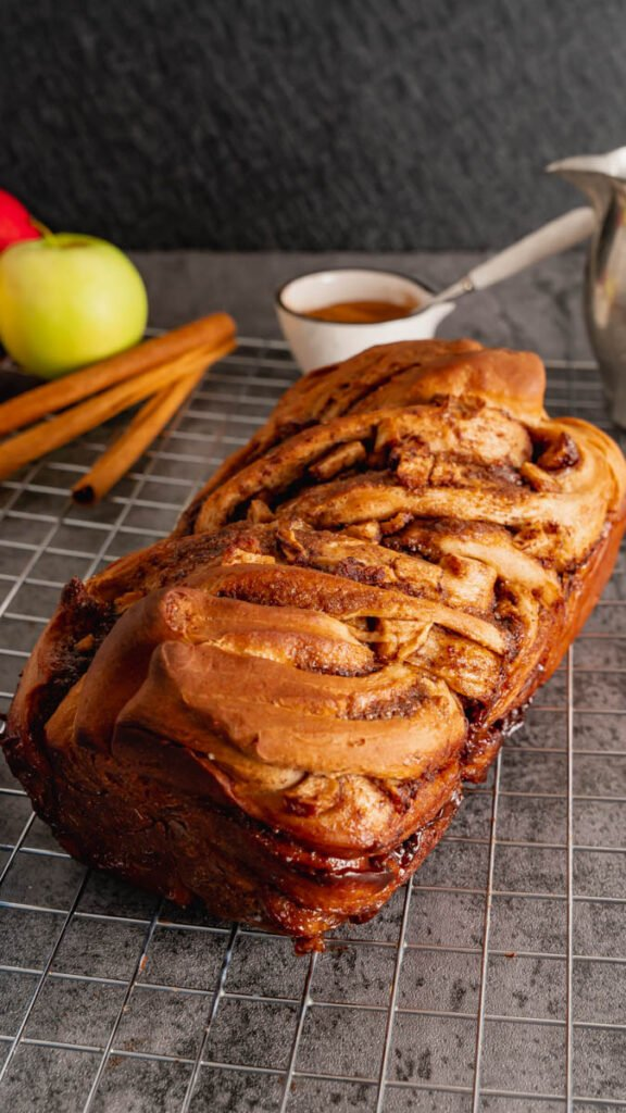 A loaf of braided apple cinnamon sweet bread fresh out of the oven resting on a wire rack to cool