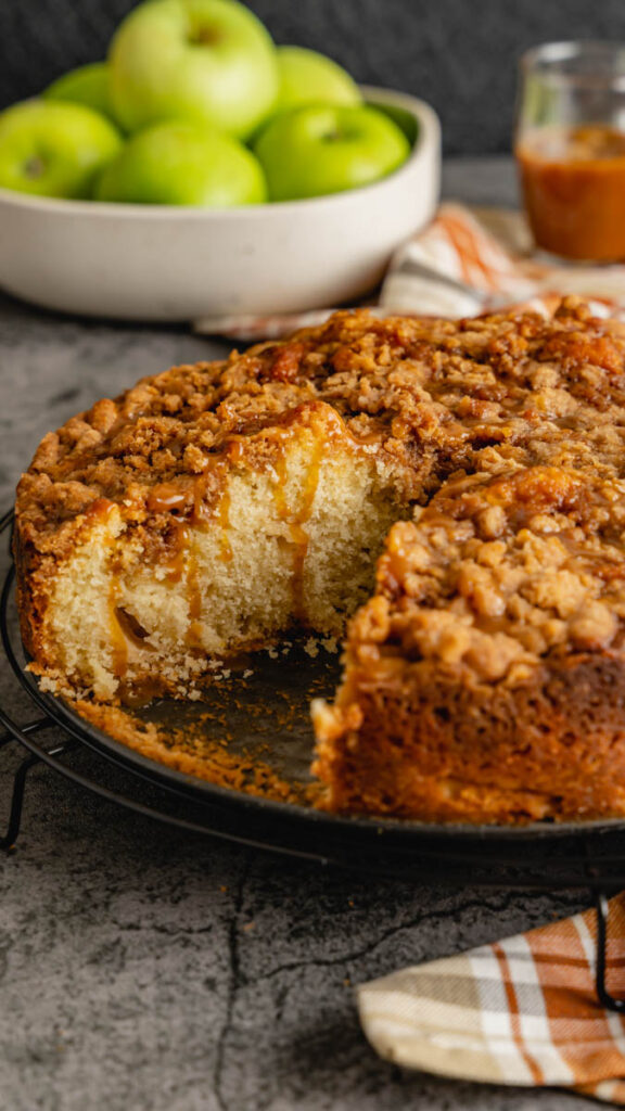 Coffee cake with a slice cut out of it resting on the bottom pan of the springform cake pan.