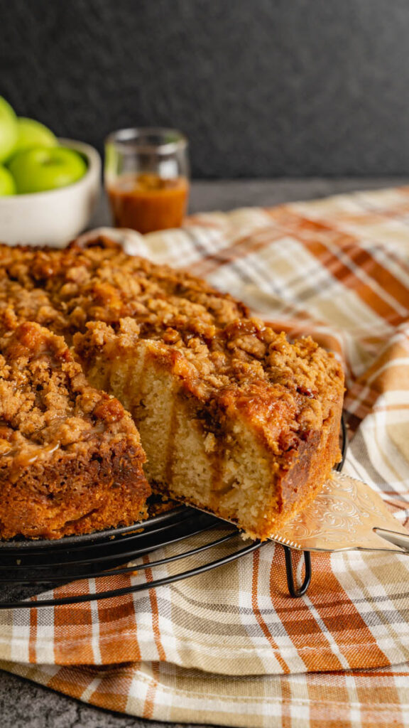 A slice of caramel apple coffee cake being taken out of a 9 inch round coffee cake.