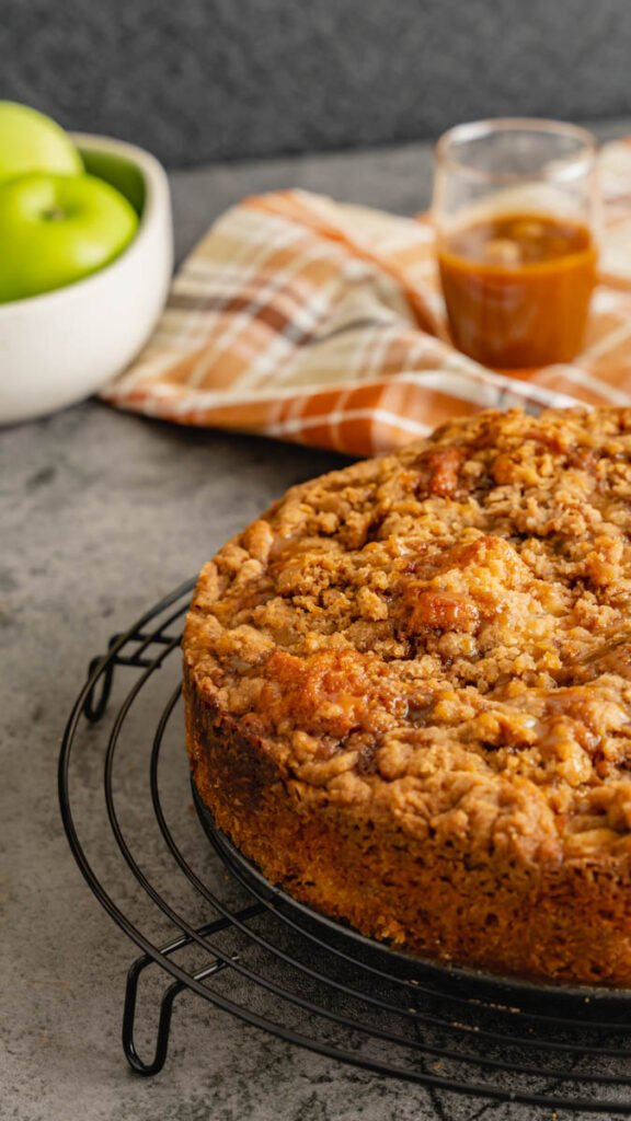 Coffee cake resting on a round wire cooling rack with Granny Smith apples in the background.