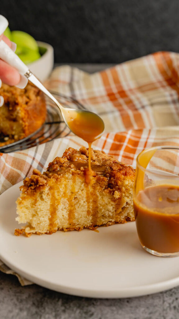 Salted caramel sauce being drizzled with a spoon on top of a slice of coffee cake.
