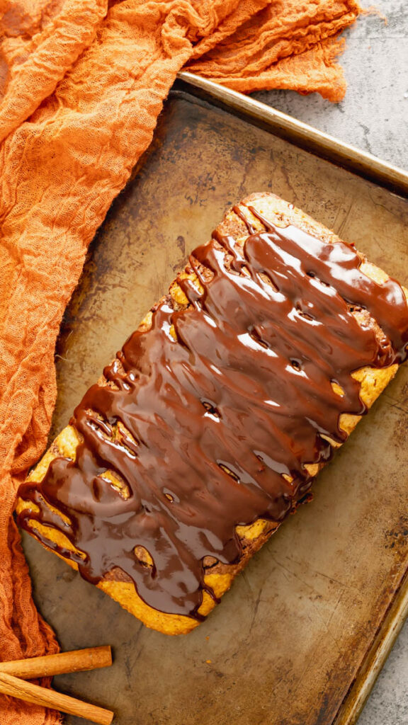 Top view of a whole pumpkin marble cake with ganache topping.