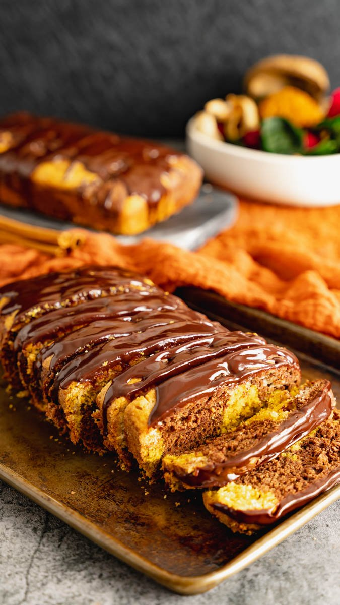 Chocolate pumpkin marble cake sliced into thick slices and topped with chocolate ganache.