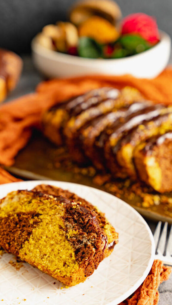 Two slices of chocolate pumpkin spice marble cake on a white plate with sliced cake in the background.