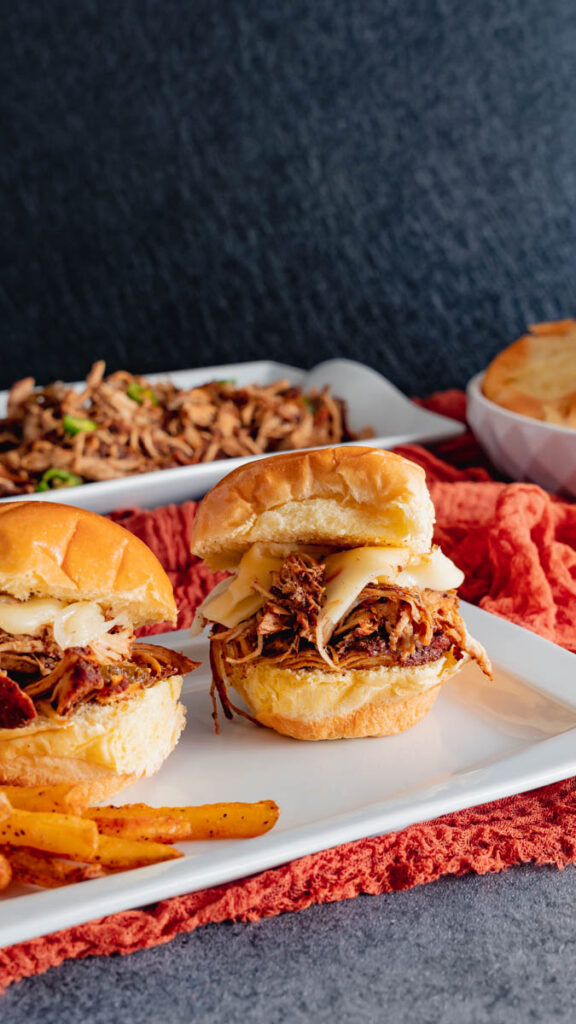 Slider buns with jerk pulled chicken and pepper jack cheese.