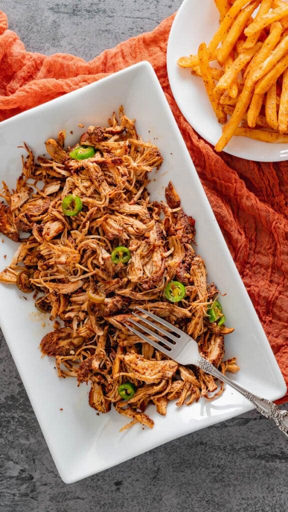 Shredded jerk chicken with sliced Serrano peppers on serving tray.