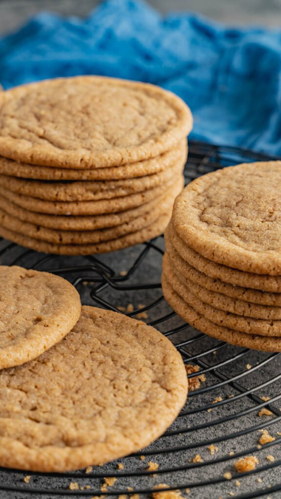 Thin and chewy brown sugar cookies stacked on a round cooling rack.