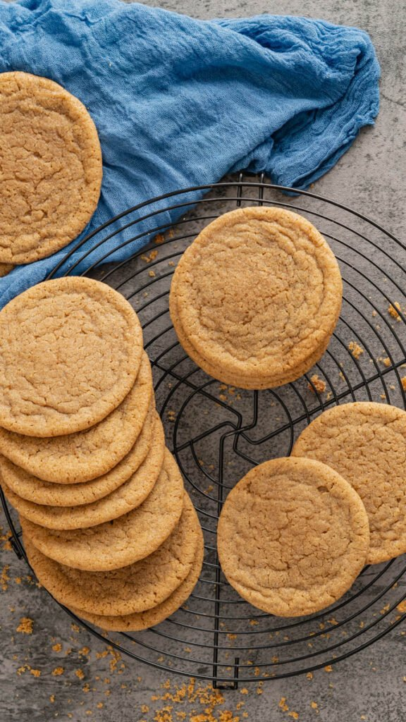 Brown sugar cookies spread out on round cooling rack with a blue linen in the background.