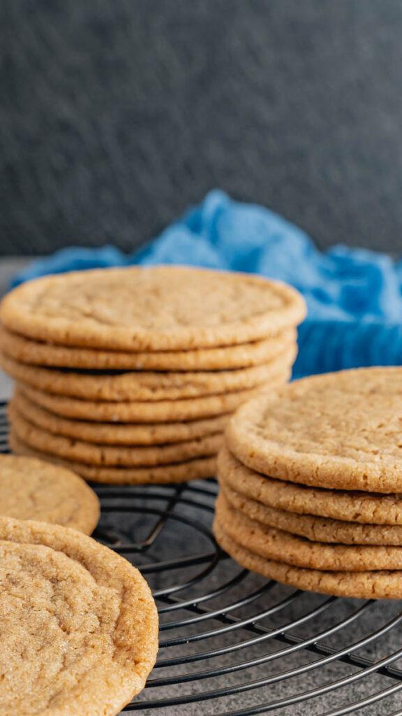Two stacks of brown sugar cookies on black cooling rack.