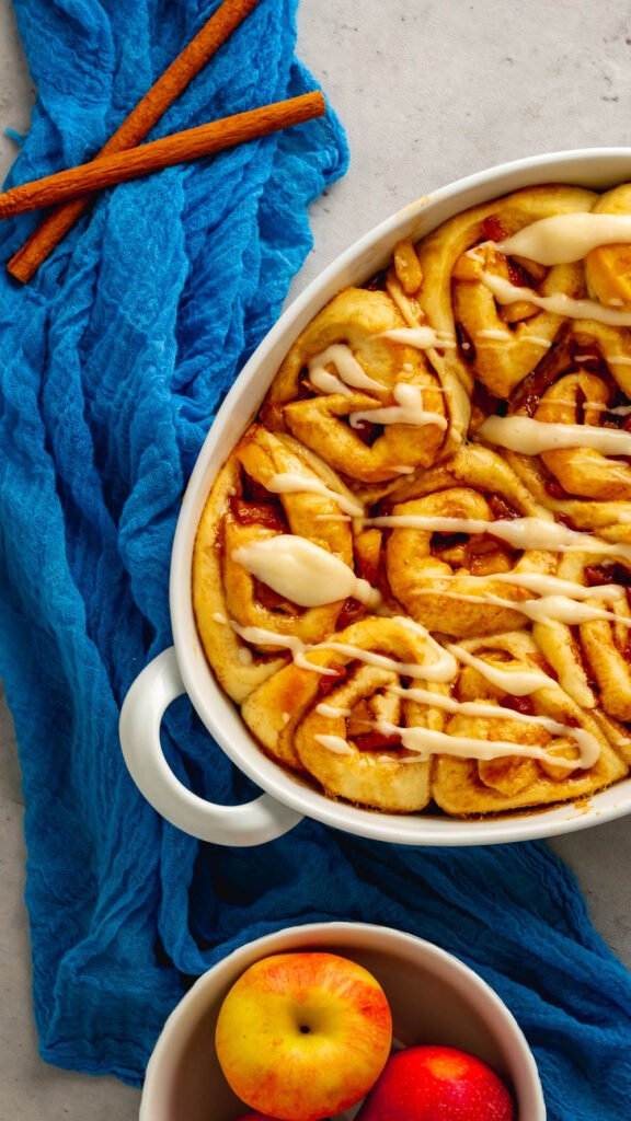 An oval baking dish with apple cider cinnamon rolls with a cream cheese icing.