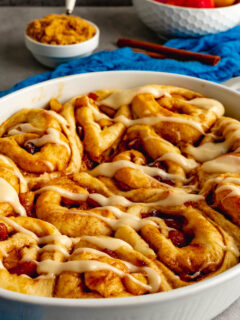 A 9 inch oval baking dish with apple cider cinnamon rolls.