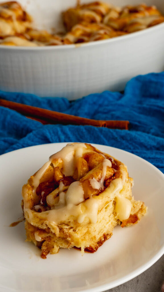 A cinnamon roll made with apple cider that is drizzled with apple cider cream cheese icing.