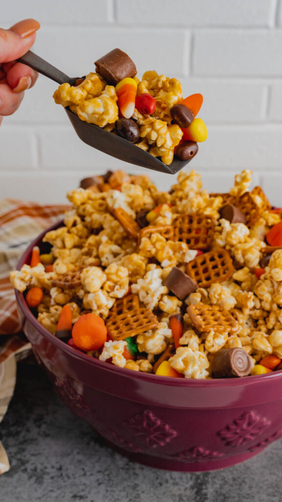 A scoop of caramel popcorn with candy corn and pretzels.