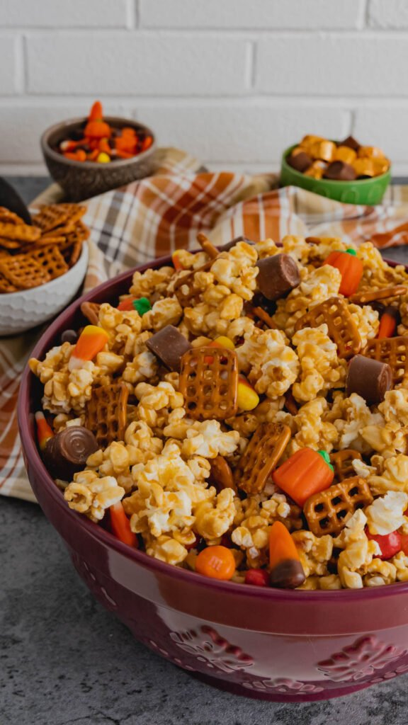 Pretzel snaps mixed into a bowl of caramel popcorn with Rolo's, candy corn, and M&M's.